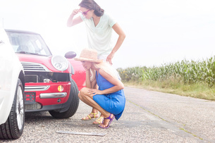 Tensed women looking at damaged cars on road against clear skyの写真素材 [FYI03656400]