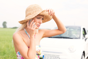 Frustrated woman using cell phone by broken down carの写真素材 [FYI03656402]