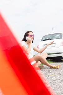 Frustrated woman using cell phone while sitting by broken down carの写真素材 [FYI03656403]