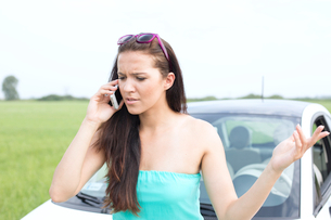 Frustrated woman using cell phone against broken down carの写真素材 [FYI03656405]