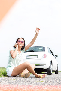 Frustrated woman hitchhiking while using cell phone by broken down carの写真素材 [FYI03656407]