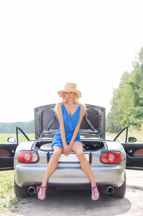 Full length portrait of woman sitting on convertible trunk against clear skyの写真素材 [FYI03656409]