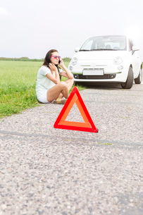 Tensed woman using cell phone while sitting by broken down carの写真素材 [FYI03656410]