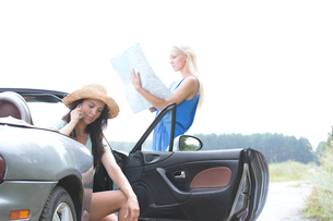 Woman using cell phone in convertible while friend reading map on roadの写真素材 [FYI03656417]