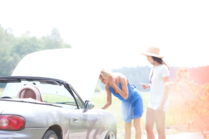 Female friends examining broken down car on country roadの写真素材 [FYI03656420]