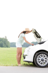 Side view of woman examining broken down car on country roadの写真素材 [FYI03656422]