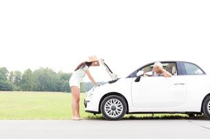 Woman looking at female friend repairing broken down car on country roadの写真素材 [FYI03656423]