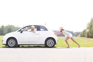 Woman pushing broken down car on country roadの写真素材 [FYI03656426]
