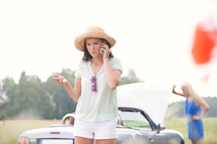 Worried woman using cell phone while friend examining broken down car outdoorsの写真素材 [FYI03656428]