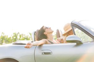Happy woman enjoying road trip in convertible with friendの写真素材 [FYI03656431]