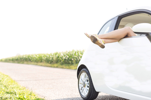 Low section of woman relaxing in car on country roadの写真素材 [FYI03656456]