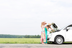 Female friends examining broken down car on country road against clear skyの写真素材 [FYI03656467]