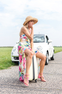 Irritated woman sitting on luggage by broken down car on country roadの写真素材 [FYI03656470]
