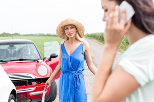 Angry woman looking at female using cell phone by damaged cars on roadの写真素材 [FYI03656474]