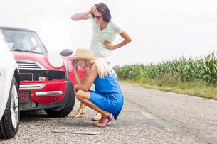 Tensed women looking at damaged cars on road against clear skyの写真素材 [FYI03656476]