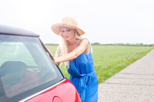 Woman pushing broken down car on country road against clear skyの写真素材 [FYI03656479]