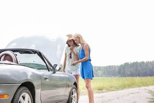 Women examining broken down car on sunny day against clear skyの写真素材 [FYI03656491]