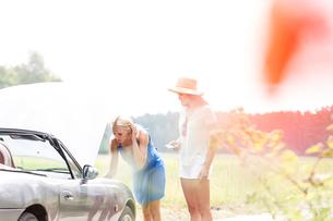 Friends repairing broken down car on sunny dayの写真素材 [FYI03656494]