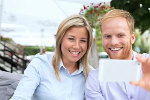 Happy business couple taking selfie at outdoor restaurantの写真素材 [FYI03656529]