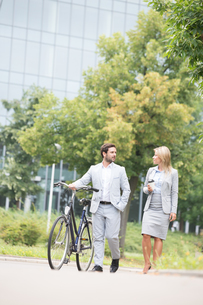Businesspeople with bicycle conversing while walking on streetの写真素材 [FYI03656541]