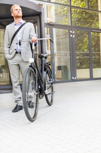 Businessman with bicycle standing outside office buildingの写真素材 [FYI03656547]