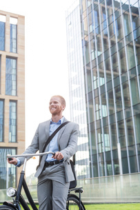 Happy businessman with bicycle standing outside office buildingの写真素材 [FYI03656551]