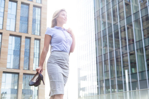 Low angle view of confident businesswoman holding high heels while standing outside office buildingsの写真素材 [FYI03656559]