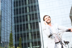 Low angle view of businessman answering mobile phone while sitting on bicycle outdoorsの写真素材 [FYI03656560]
