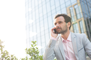 Businessman answering mobile phone outside office buildingの写真素材 [FYI03656570]