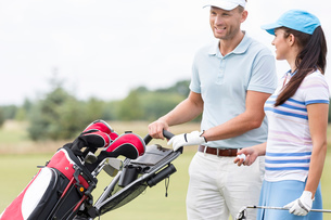 Happy friends with bag talking at golf courseの写真素材 [FYI03656645]