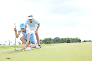 Man with woman aiming ball on golf course against skyの写真素材 [FYI03656673]