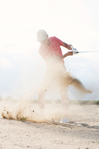Middle-aged man splashing sand while playing at golf courseの写真素材 [FYI03656694]