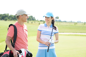Happy male and female golfers communicating at courseの写真素材 [FYI03656695]
