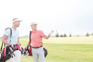 Man showing something to friend at golf course against clear skyの写真素材 [FYI03656715]
