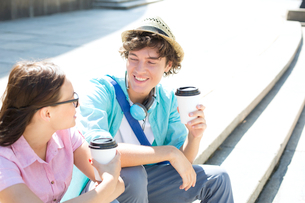 Happy friends holding disposable coffee cups while sitting on steps outdoorsの写真素材 [FYI03656747]