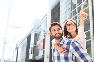 Smiling woman pointing away while enjoying piggyback ride on man in cityの写真素材 [FYI03656786]