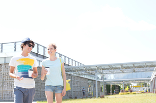Smiling couple holding disposable cups while walking at parkの写真素材 [FYI03656791]