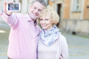 Happy middle-aged couple taking selfie through smart phone in cityの写真素材 [FYI03656833]