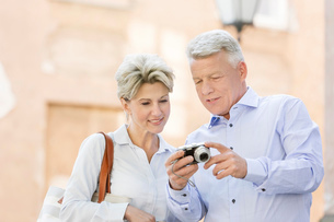 Smiling middle-aged couple reviewing photos on digital camera outdoorsの写真素材 [FYI03656846]