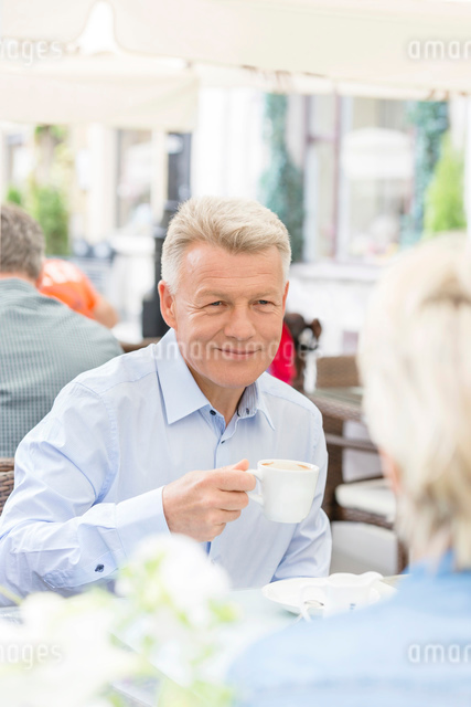 Smiling middle-aged man having coffee with woman at sidewalk cafeの写真素材 [FYI03656872]