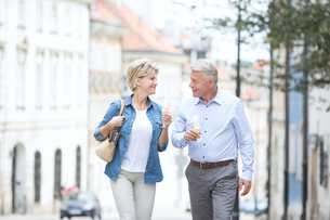 Happy middle-aged couple looking at each other while holding ice cream cones in cityの写真素材 [FYI03656891]