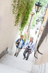 High angle view of middle-aged couple holding hands while climbing steps outdoorsの写真素材 [FYI03656894]