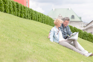Middle-aged couple reading map while sitting at parkの写真素材 [FYI03656898]