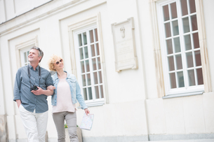 Happy middle-aged tourist couple walking arm in arm by buildingの写真素材 [FYI03656906]