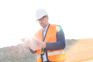 Male supervisor reading clipboard at construction site on sunny dayの写真素材 [FYI03656913]