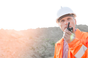 Confident supervisor using walkie-talkie on construction site against clear skyの写真素材 [FYI03656916]