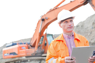 Supervisor looking away while holding clipboard at construction siteの写真素材 [FYI03656919]