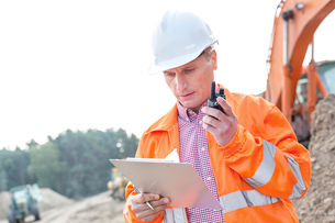 Supervisor reading clipboard while using walkie-talkie at construction siteの写真素材 [FYI03656920]