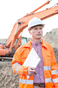 Architect looking away while holding clipboard at construction siteの写真素材 [FYI03656924]