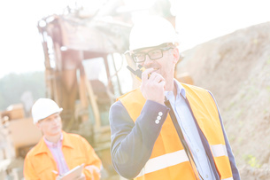 Happy engineer using walkie-talkie on construction site with colleague in backgroundの写真素材 [FYI03656925]